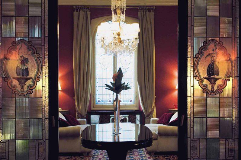Détail du salon avec fenêtre à deux portes en bois laqué blanc avec un profil classique
