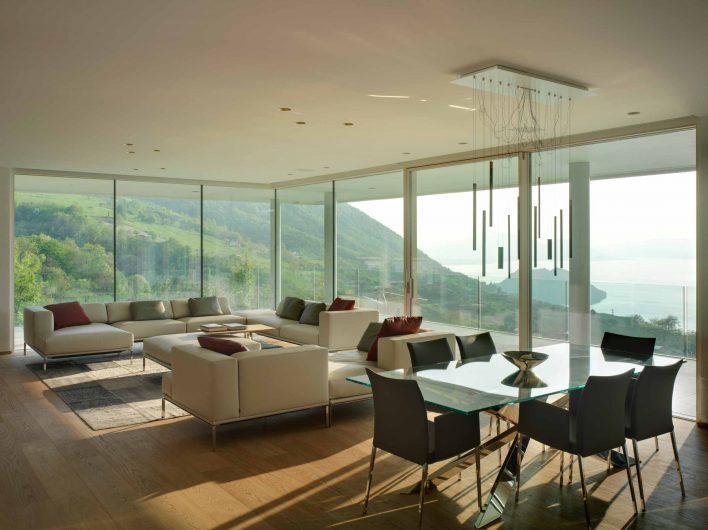 Paroi en verre du salon avec fixations pleine hauteur et porte coulissant laqué blanc