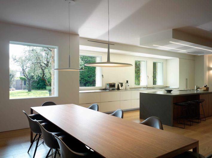 Vue de la cuisine ouverte et de la salle à manger avec fenêtres intégrées laquées blanches fixes et affleurantes