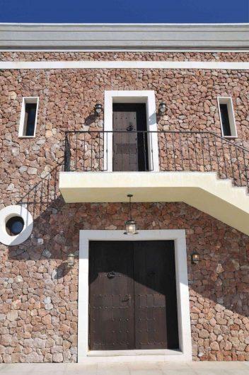 Vue de la façade de la résidence avec double porte aveugle au premier plan