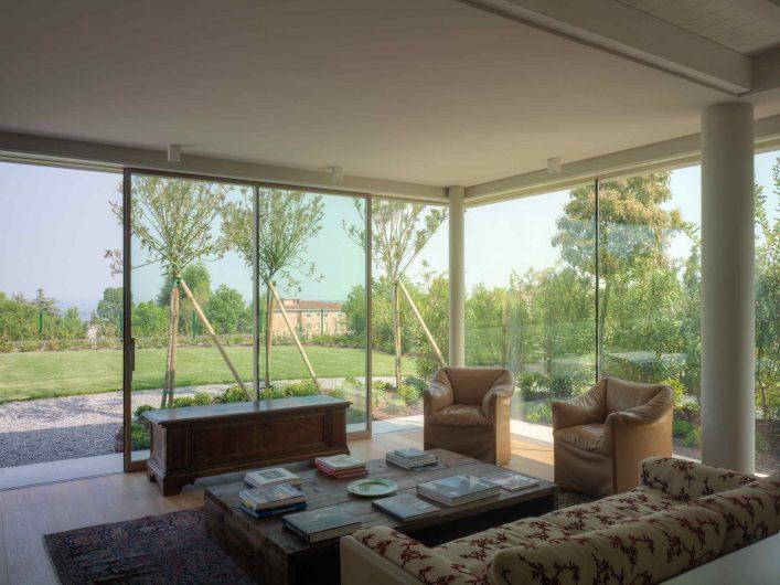 Vue de la pièce à vivre avec un exemple de porte coulissant laqué et d'angle en verre encastré