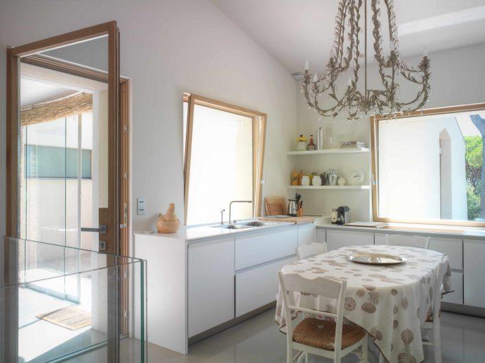 Vue de la cuisine avec porte d'entrée vitrée et deux fenêtres à imposte