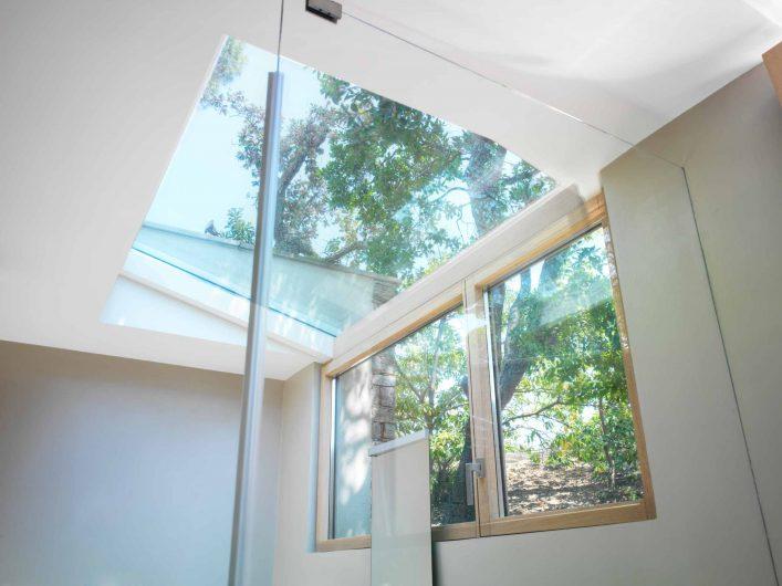 Vue de la fenêtre à double battant de la salle de bain de la villa avec puits de lumière vitré
