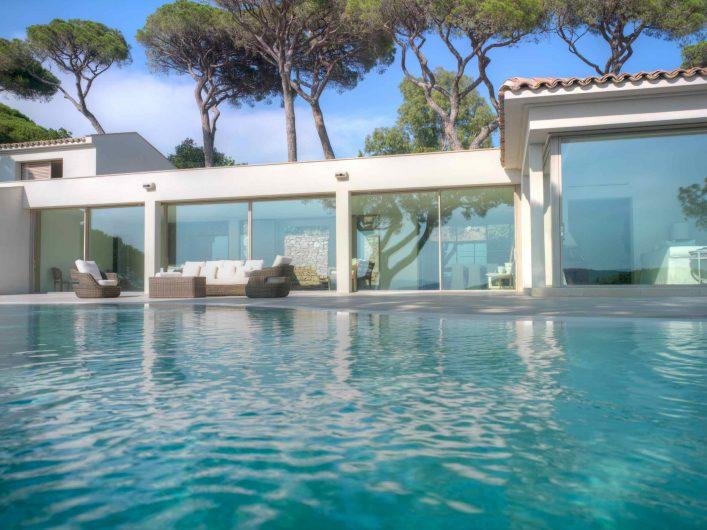 Vue de face extérieure des portes coulissantes du salon avec piscine au premier plan