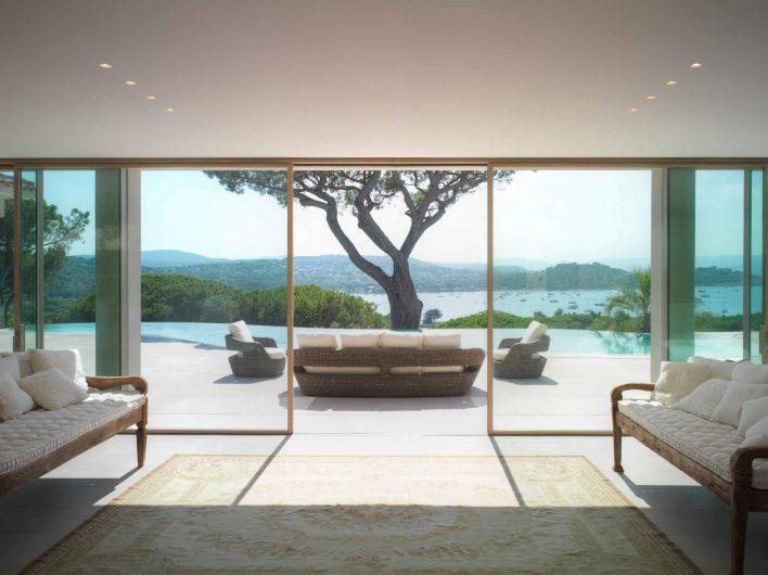 Vue de face de la porte coulissant avec quatre portes ouvertes dans le salon de la villa