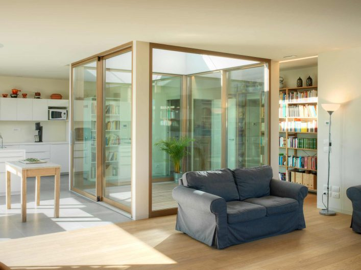 Vue sur l'espace ouvert de la Villa Firenze avec cour intérieure fermée par des portes coulissantes et des fenêtres fixes