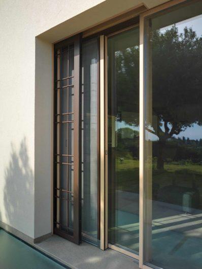 Vue extérieure de porte coulissant du salon avec moustiquaire et grille en fer coulissant latéralement