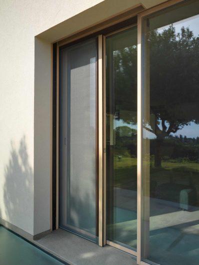 Vue extérieure de porte coulissant en bois avec moustiquaire coulissante latérale