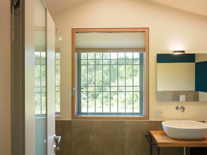 Vue de la fenêtre de la salle de bain à une porte avec moustiquaire et grille en fer