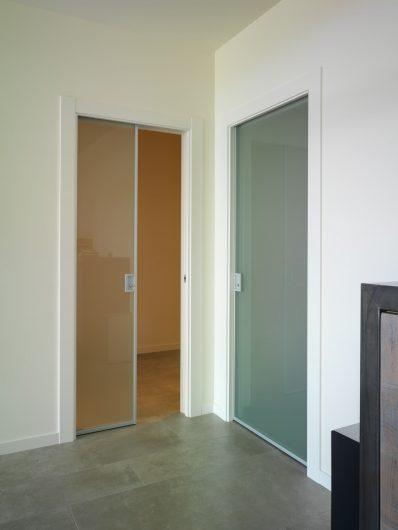 Vue de deux portes coulissantes intérieures en aluminium et verre