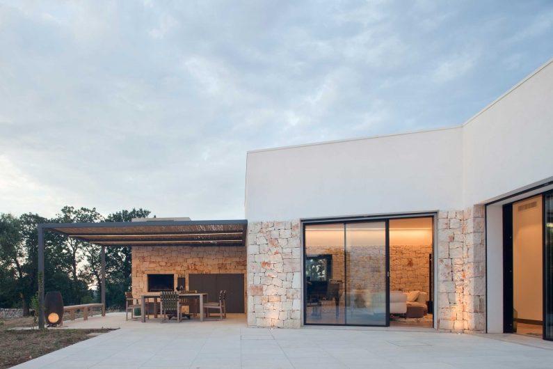 Vue du patio extérieur avec portes levantes et coulissantes à deux portes asymétriques en sapin teinté foncé