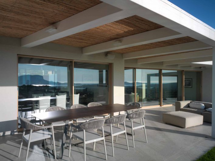 Vue du porche au coucher du soleil avec portes levantes et coulissantes en chêne effet naturel