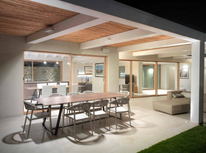 Vue nocturne du porche avec portes levantes et coulissantes en chêne à deux et quatre portes