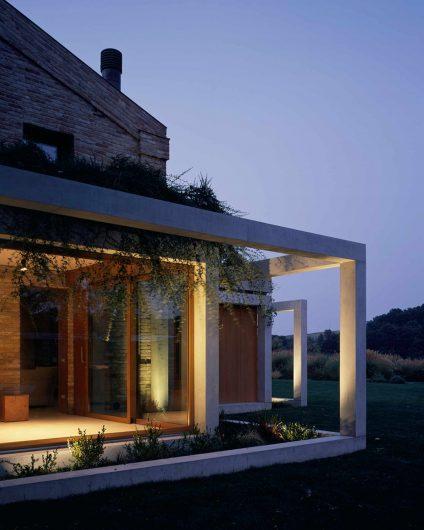 Vue de l'élévation au coucher du soleil, détail d'une fenêtre en verre fixe et de la porte coulissante en chêne