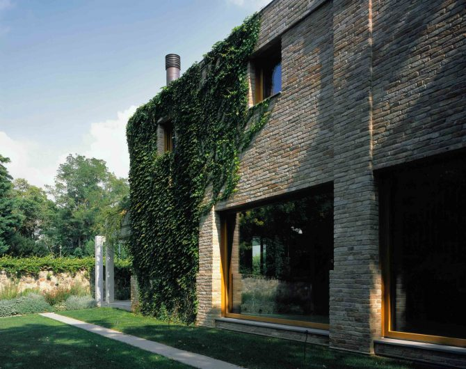 Vue de la façade latérale en briques recyclées avec fenêtres fixes en bois de chêne