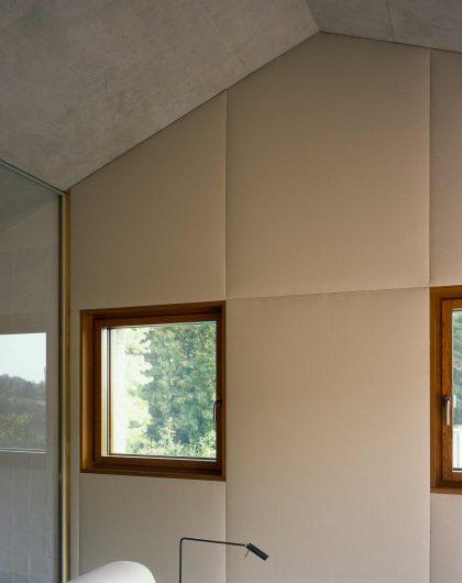 Vue du mur intérieur d'une pièce couverte de boiserie, avec une seule fenêtre en chêne