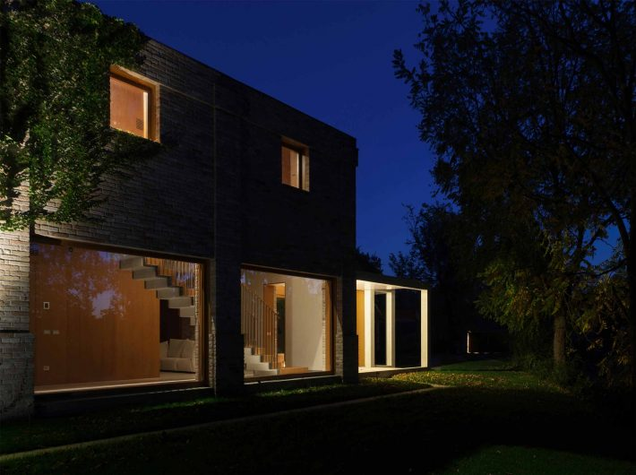 Vue en soirée avec baies vitrées fixes et fenêtres Skyline éclairées