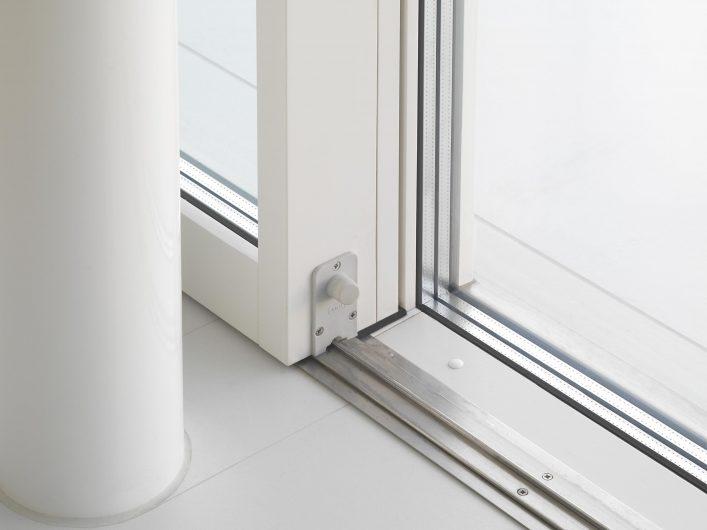Détail de la porte coulissant avec rail bas et triple vitrage