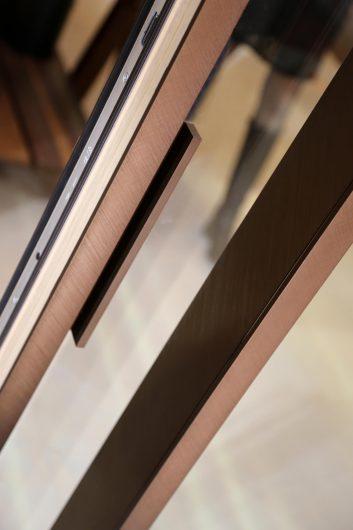 Détail de la poignée d'une porte coulissant d'aluminium bronze brossé
