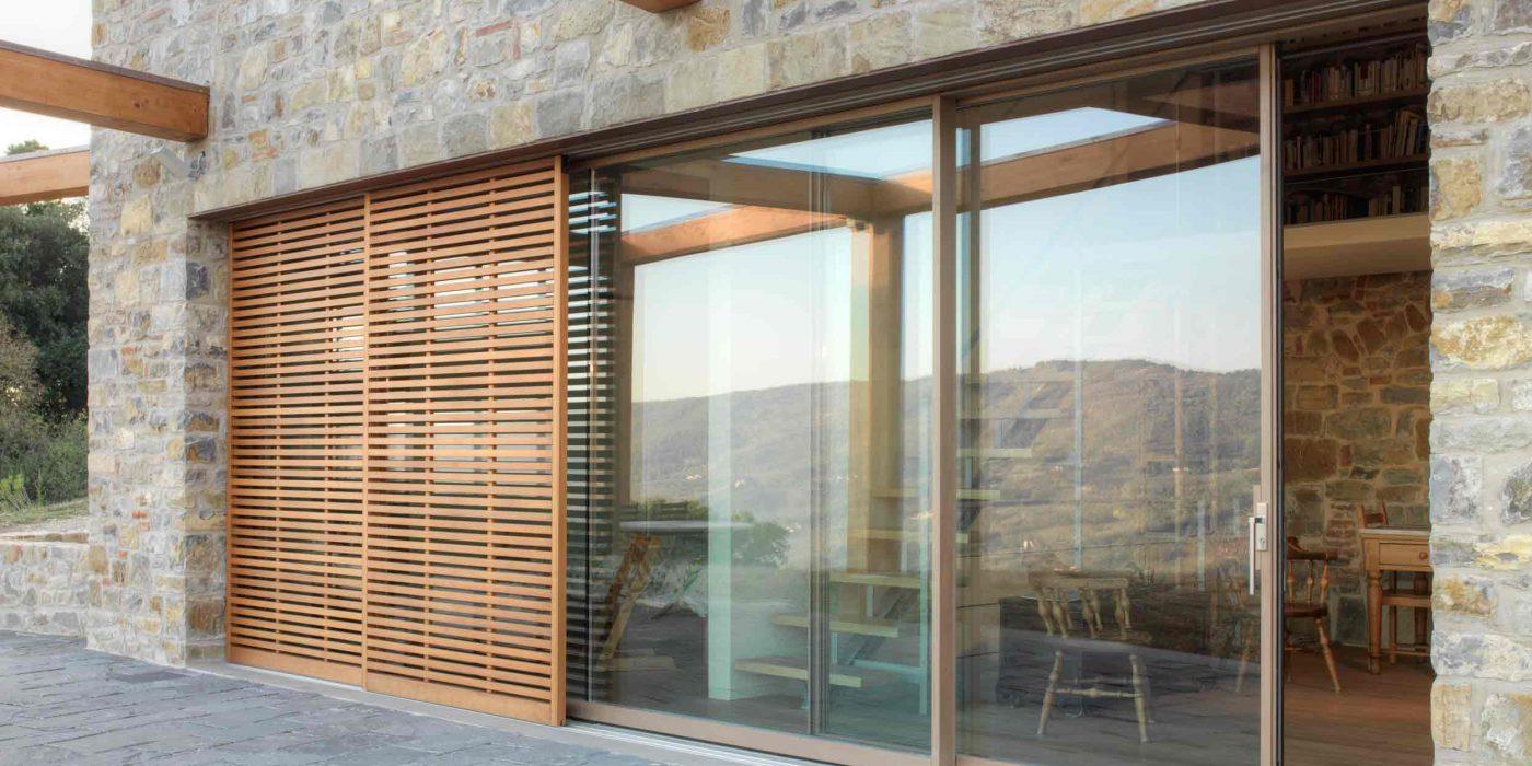 Vue extérieure d'une porte coulissant en bois avec parasol à lattes