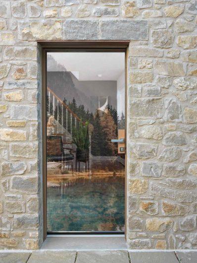 Vue extérieure d'une porte d'entrée avec poignée traversante et verre structurel à effet vitrum