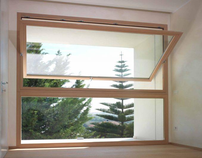 Vista frontale di una finestra a bilico in legno con finitura naturale