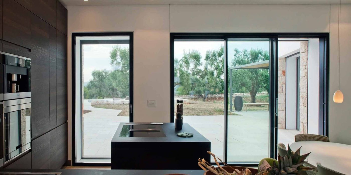 Vista della cucina con porta finestra Skyline Door e alzante scorrevole a due ante asimmetriche