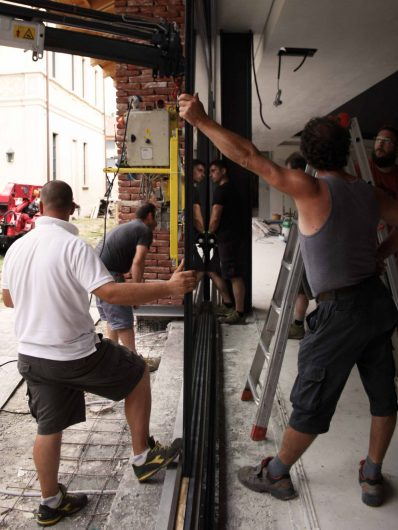 View of a group of technicians engaged in the installation of a fixed glass window