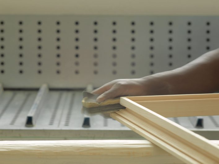 View of a carpenter while sanding a profile